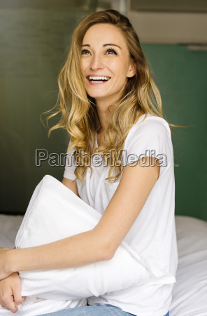 laughing blond woman sitting on bed