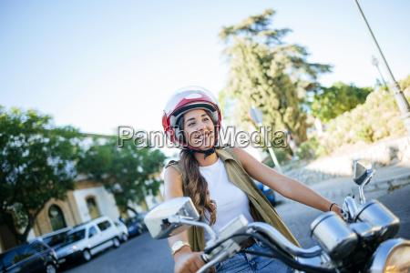 glueckliche junge frau mit motorrad