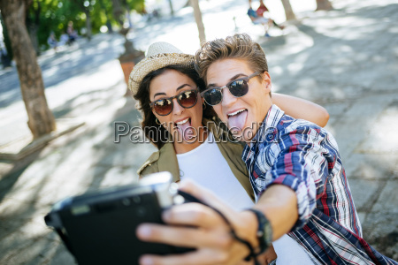 young couple sticking out tongues while