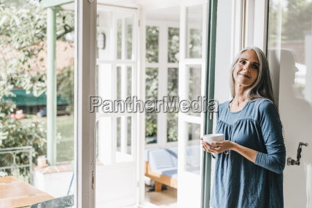 smiling woman leaning at door frame