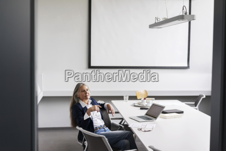 senior businessswoman sitting at conference table