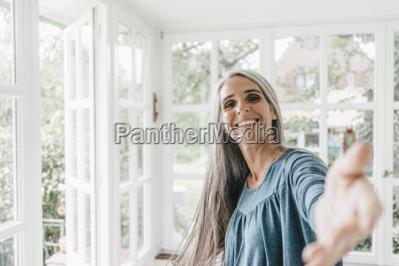 portrait of smiling woman inviting viewer
