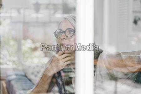 pensive woman sitting in winter garten