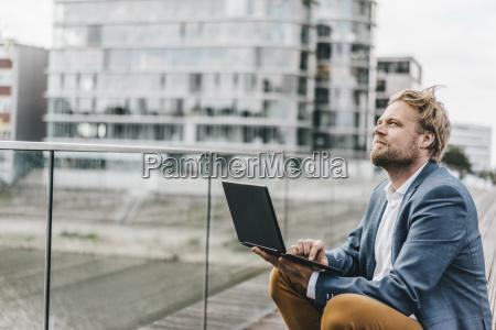 businessman sitting on bridge using laptop