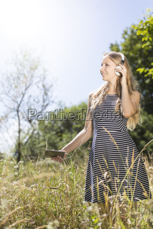smiling young woman standing on meadow