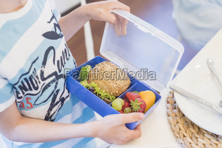 boy packing lunch box with healthy