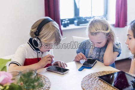 drei kinder mit mobilen geraeten