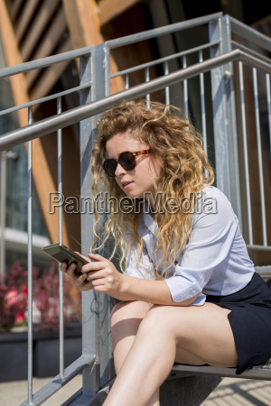businesswoman sitting on stairs using cell