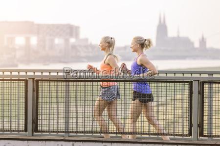 zwei junge frauen laufen auf bruecke