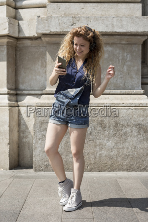 smiling young woman with headphones and