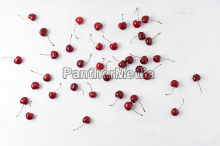 sweet cherries scattered on white ground