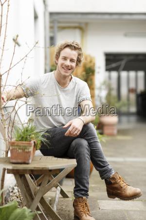 young man sitting in backyard smiling