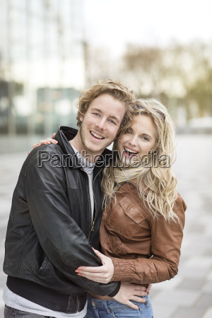 laughing young couple embracing in city