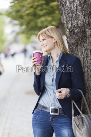 smiling blond businesswoman with coffee to