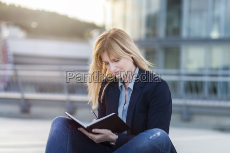 businesswoman with notebook writing down something