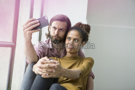 young couple sitting on window sill