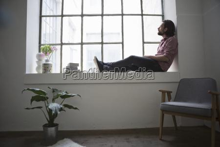 man sitting on window sill looking