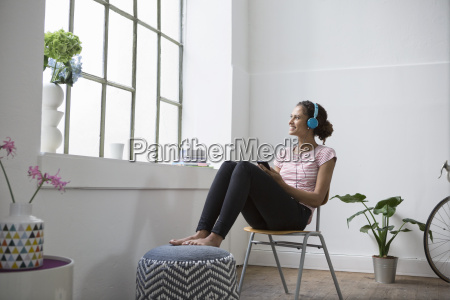 young woman sitting on chair listening