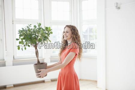 laechelnde frau haelt pflanze in leerer
