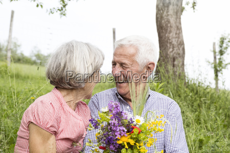 happy senior couple with bunch of