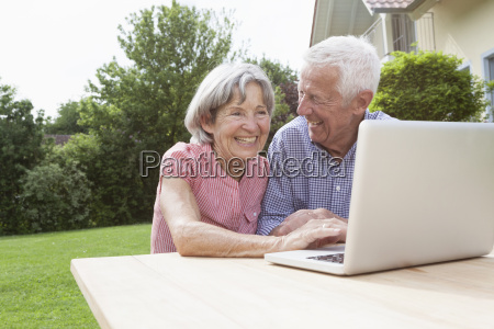 happy senior couple using laptop in