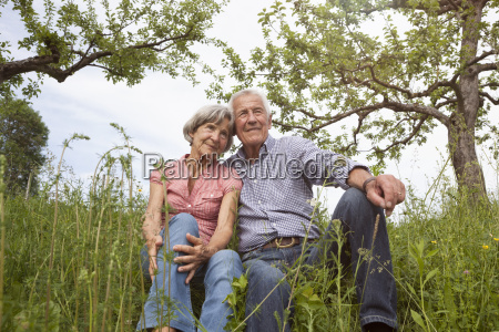 relaxed senior couple sitting in meadow