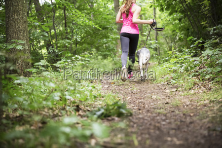 young woman jogging with dog in