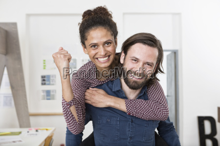 man carrying happy woman piggyback in