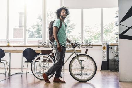 young man with rucksack pushing bicycle
