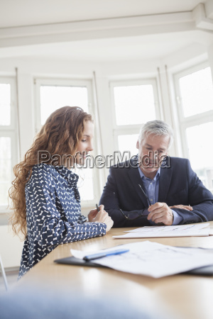businessman and woman at desk discussing