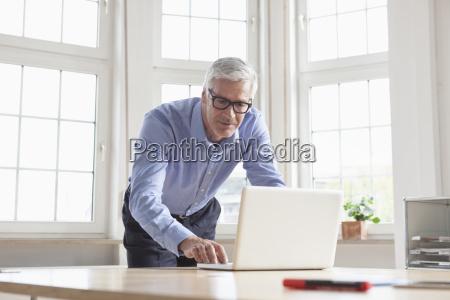 reifer geschaeftsmann mit laptop am bueroschalter
