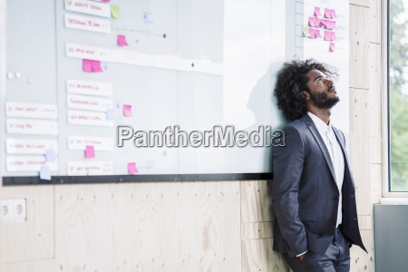 young businessman leaning against white board