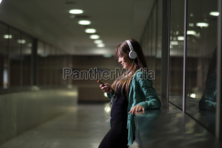 young woman with headphones and smartphone