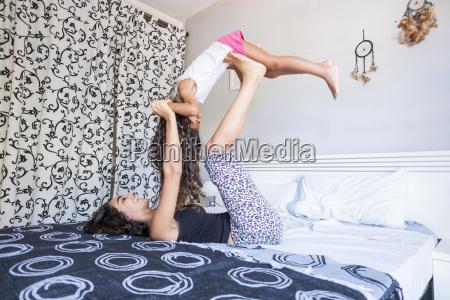 teenage girl lying on bed balancing