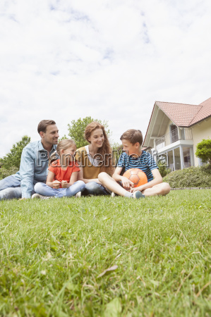 smiling family sitting in garden with