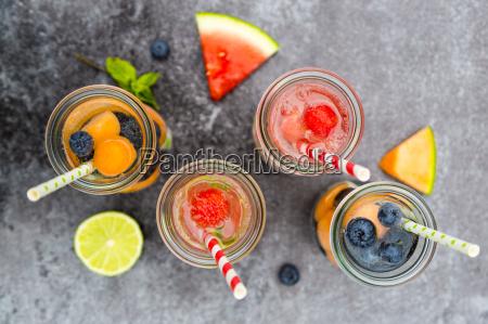 karaffen von verschiedenen fruechten infundiertes wasser