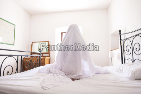 woman with bed sheet sitting on