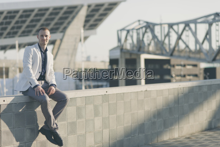 fashionable businessman sitting on wall at