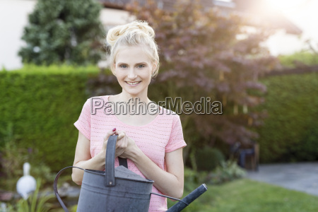 portrait of blond woman holding watering