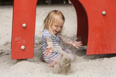 blondes kleines maedchen im sandkasten auf