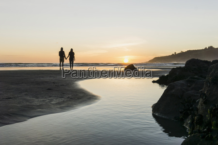 silhouette of couple standing hand in