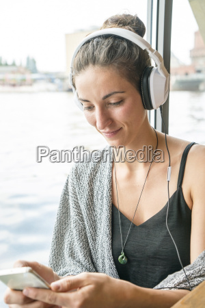 smiling young woman listening music with
