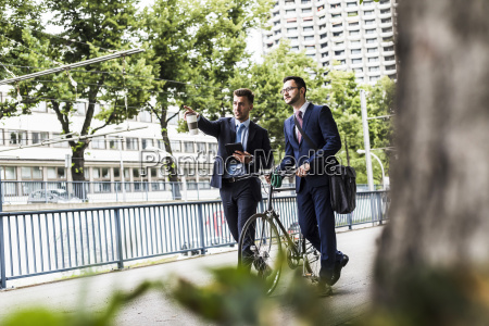 businessmen walking with bicycle in the