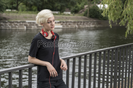 young woman with headphones leaning on