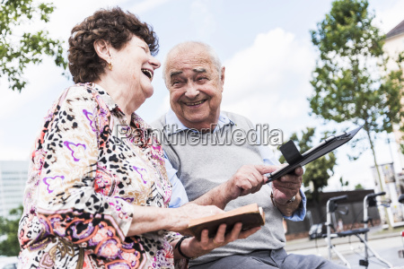 laughing senior couple sitting together on