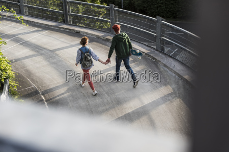 young couple with skateboard walking hand