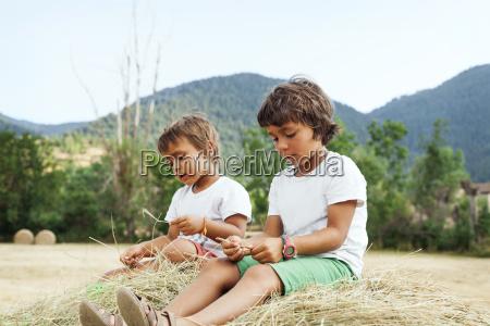 two little boys sitting on bale