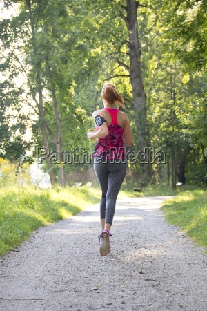 young woman jogging with dumbbells
