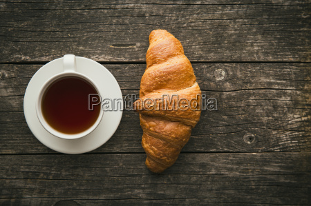 tasty buttery croissant and cup of