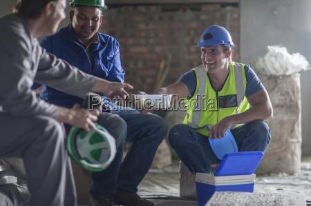 drei bauarbeiter beim mittagessen